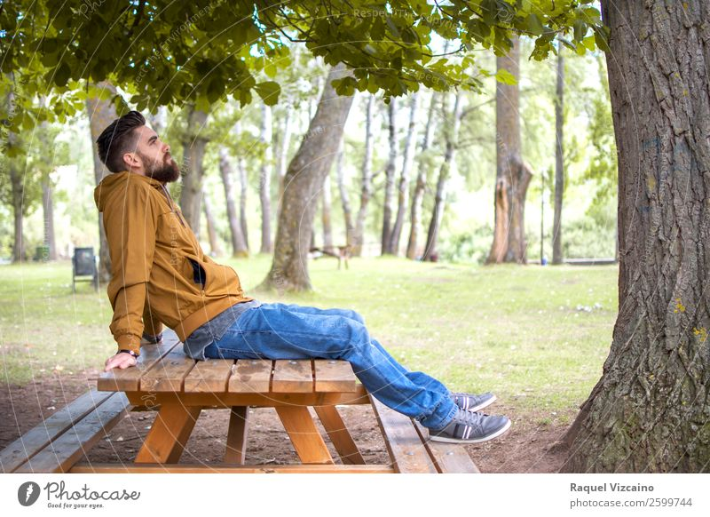 Man sitting in a park, on a picnic table Human being Nature Vacation & Travel Youth (Young adults) Green Young man Relaxation 18 - 30 years Lifestyle Adults