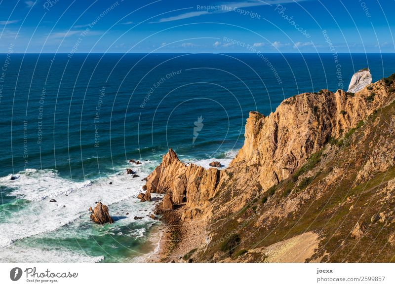 Brown rocky coast into the blue sea with waves and spray Ocean Rock Waves Landscape Sky Horizon Beautiful weather Deserted Exterior shot Day Water Summer