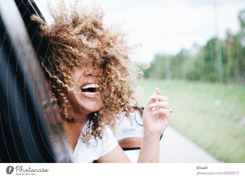 Happy woman with curly hair riding in car laughing Human being Youth (Young adults) Young woman Beautiful Joy Street Lifestyle Feminine Emotions Laughter