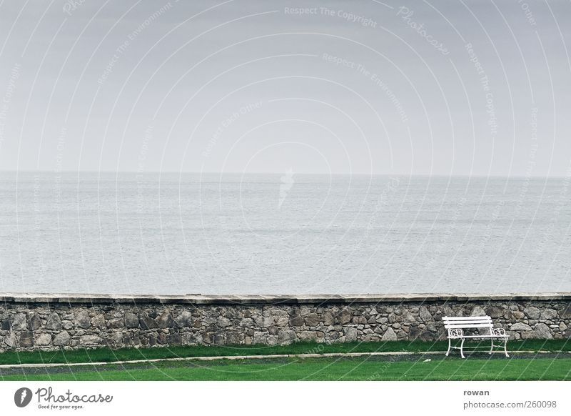 bench Landscape Bad weather Waves Coast Lakeside Ocean Dark Cold Bench Sit Seat Wall (barrier) Stone Water Grass surface Fog Park Relaxation Calm Resting point