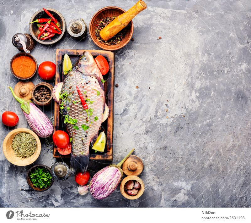 Fresh raw fish and food ingredients carp seafood fresh meal healthy cutting board cooking pepper tomato vegetable preparation spice salt diet uncooked closeup