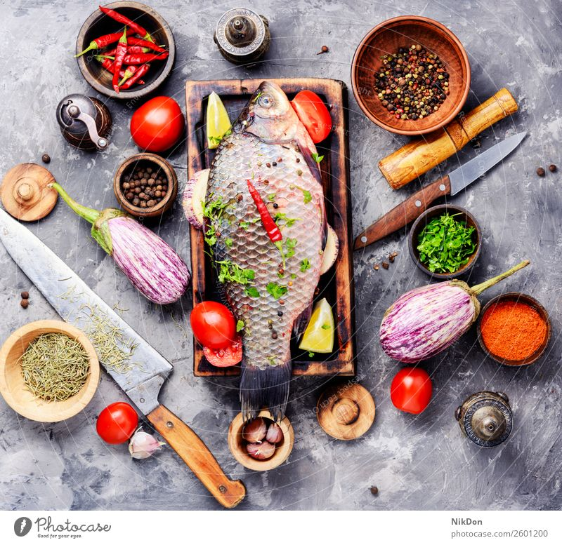 Fresh raw fish and food ingredients carp seafood fresh meal healthy cutting board cooking pepper tomato vegetable preparation spice salt diet uncooked whole