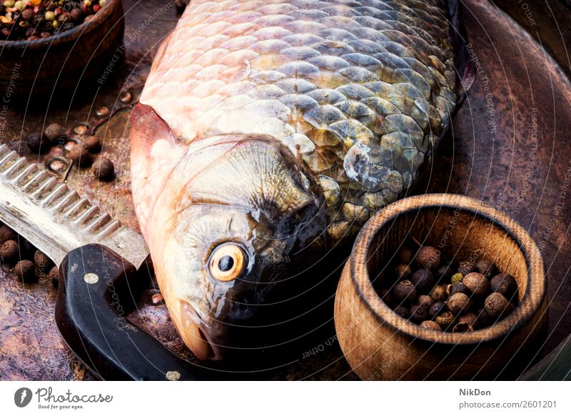 Fresh raw fish and food ingredients carp seafood fresh meal healthy cooking preparation table spice salt dinner diet pepper uncooked closeup rustic dieting