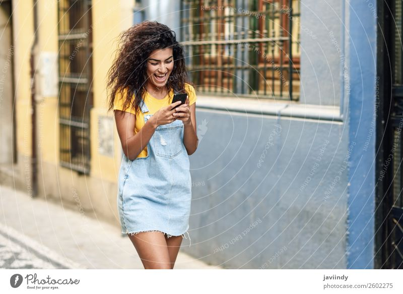 African woman walking on the street looking at her smartphone Lifestyle Style Happy Beautiful Hair and hairstyles Telephone PDA Technology Human being Feminine