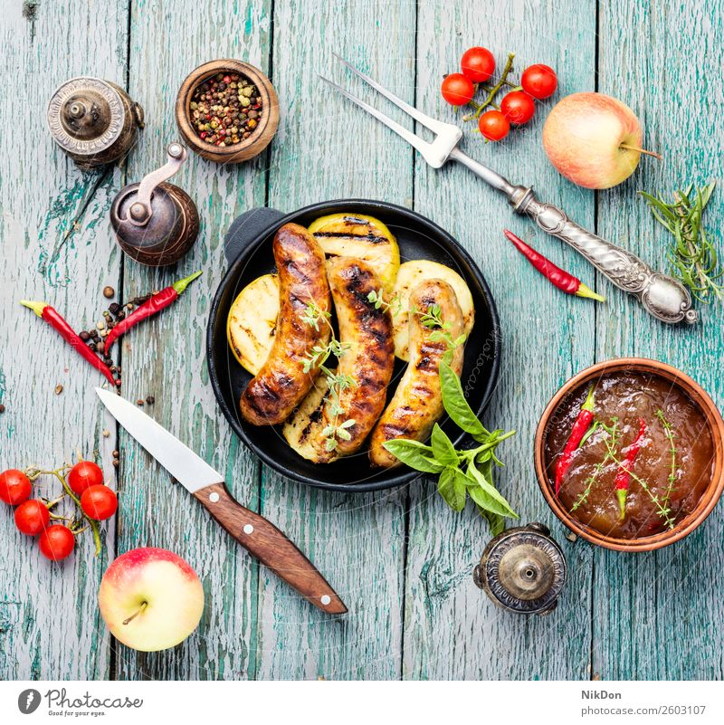 Grilled sausages in frying pan grilled meat barbecue food pork bbq meal dinner chilli roasted apple fruit beef sauce table spicy dish fried herb kitchen pepper