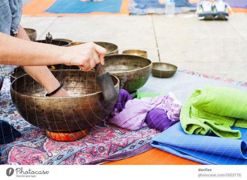 Hand playing yoga bowls outdoors. Lifestyle Wellness Relaxation Meditation Spa Music Yoga Human being 1 Street Metal Playing Healing Sound tibetan Therapy