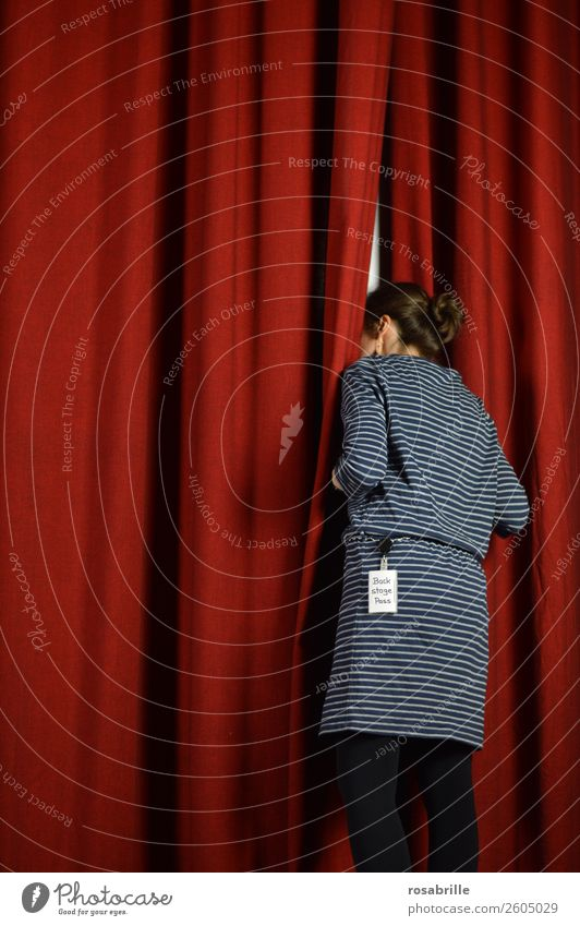 young woman in a blue dress dares to take a look behind the scenes and curiously looks behind a red theatre curtain as a symbol for background information, insights or announcements