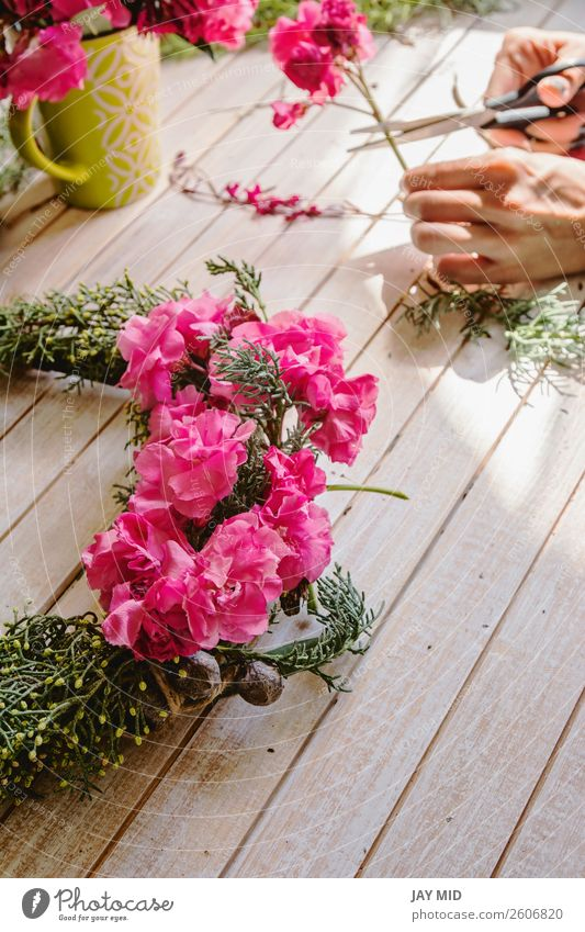 Florist at work: Creating a wooden wreath with branches pine Woman Christmas & Advent Green Hand Flower Adults Wood Natural Feasts & Celebrations Pink