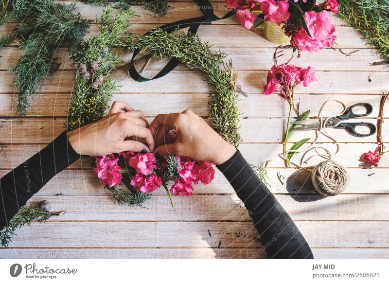 Florist at work: Creating a wooden wreath with flowers Woman Christmas & Advent Green Hand Flower Adults Natural Pink Work and employment Decoration Arrangement