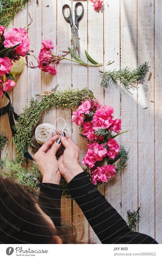Florist at work Creating a wooden wreath with pink flowers Woman Christmas & Advent Green Hand Flower Adults Natural Pink Work and employment Decoration