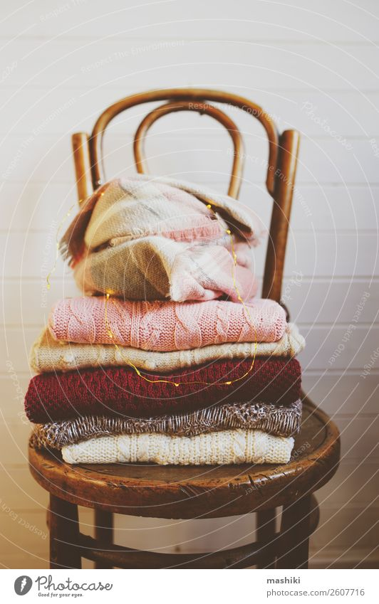 warm knitted sweaters stack on wooden chair. Colour White Winter Lifestyle Wood Warmth Autumn Style Fashion Design Clothing Soft Chair Home Cozy