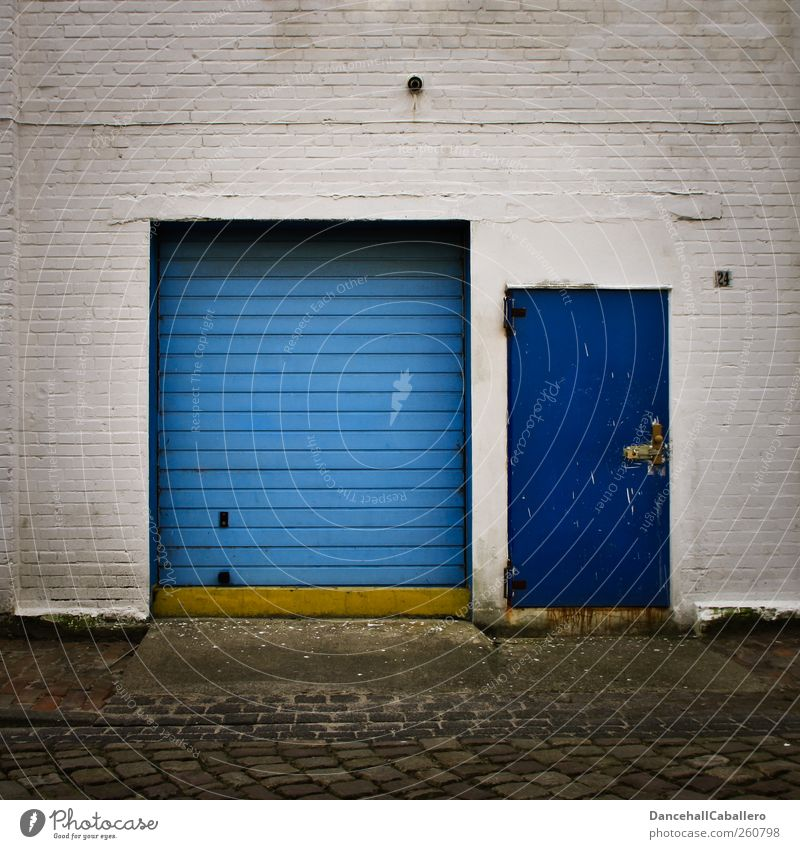 garage entrance Town House (Residential Structure) Gate Parking garage Garage Garage door Wall (barrier) Wall (building) Door Street Line Old Dark Cheap Blue