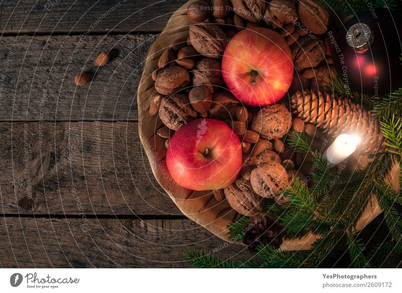 Platter with nuts and apples with Xmas decor Apple Happy Winter Decoration Table Candle Retro Tradition Christmas settings above view background candlelight