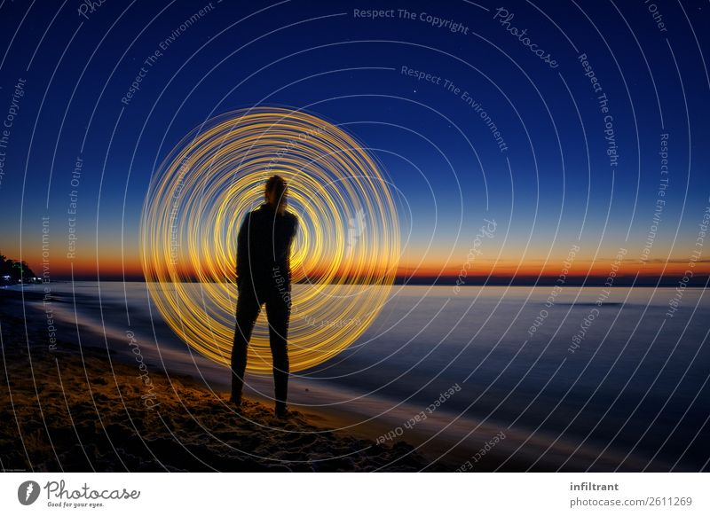 Plays of light on the beach Ocean 1 Human being Beach Line Stripe Movement Rotate Illuminate Stand Round Blue Yellow Black Esthetic Horizon Creativity Art
