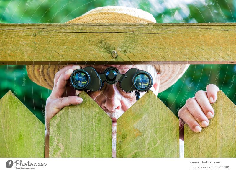 "a man looks through a fence with binoculars Human being Masculine Man Adults Male senior 1 ""Fence Paling fence"" Hat Binoculars Observe Curiosity Grouchy"