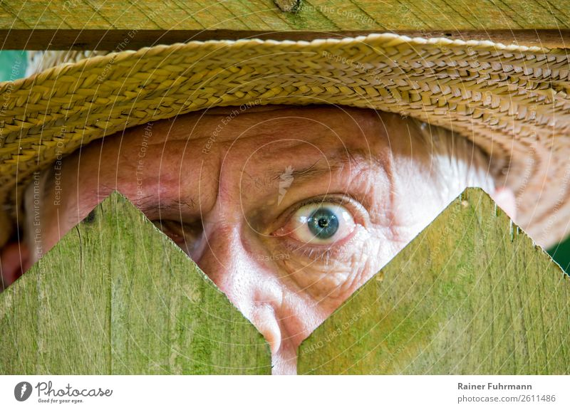 a curious neighbour stands behind a fence Human being Masculine Man Adults Eyes 1 60 years and older Senior citizen Observe Old Curiosity Emotions Moody