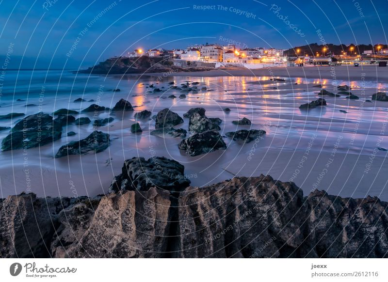 Rocks on the Atlantic beach at low tide with illuminated town in the background at dusk Beach Summer Ocean Portugal Praia das Maçãs Vacation & Travel