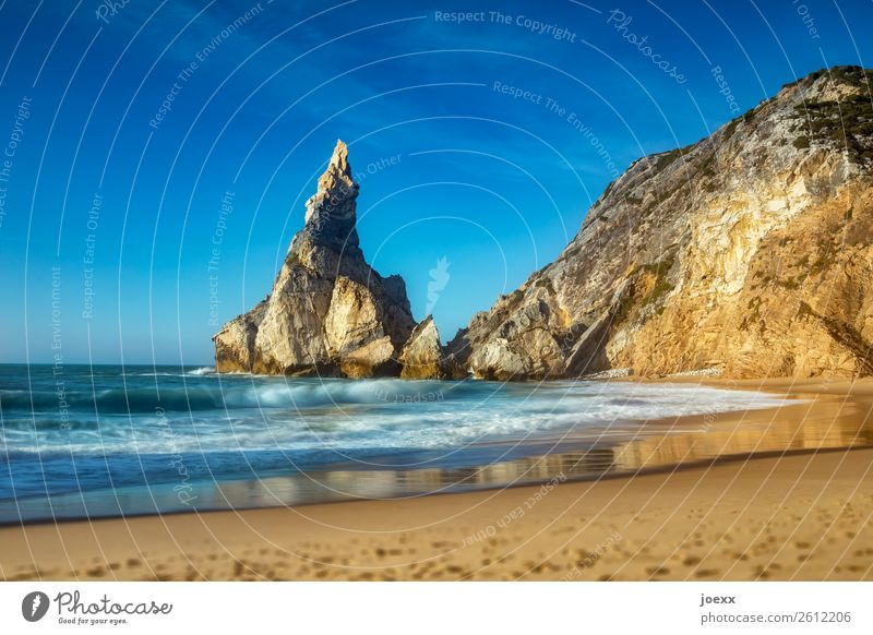 Large pointed rock on coast with sandy beach with light waves rocky coast Ocean Rock Beach Sandy beach Sky Landscape Horizon Beautiful weather Deserted