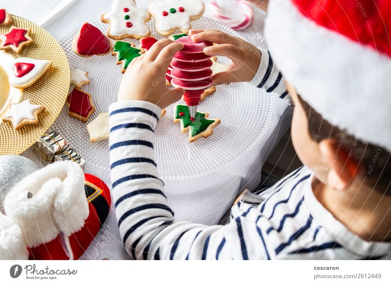 Little kid decorating Christmas biscuits at Christmas day Dough Baked goods Dessert Candy Joy Happy Leisure and hobbies Decoration Table Kitchen