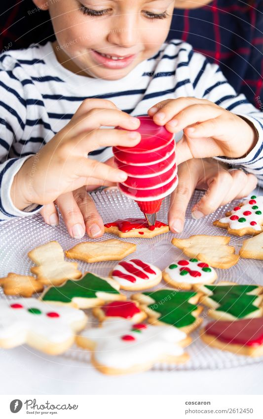 Little kid decorating Christmas biscuits at Christmas day Dough Baked goods Joy Happy Decoration Table Kitchen Feasts & Celebrations Christmas & Advent Child