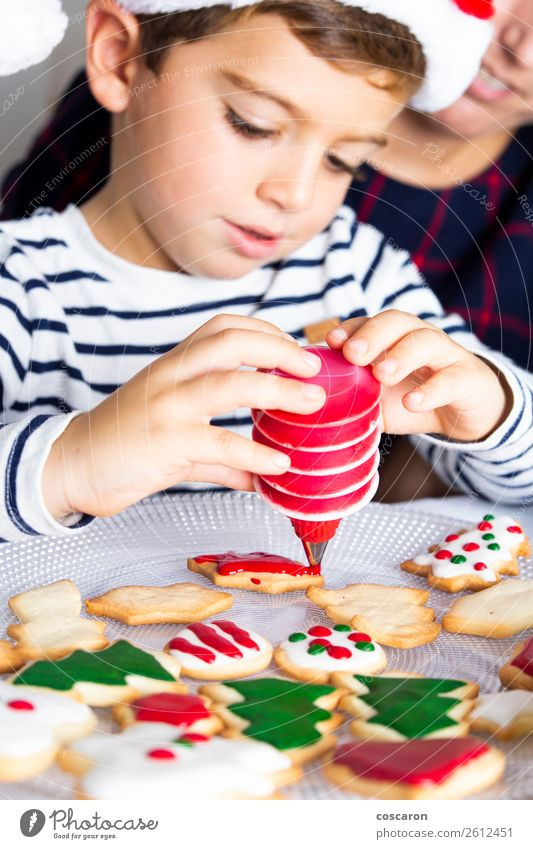 Little kid decorating Christmas biscuits at Christmas day Child Human being Youth (Young adults) Young woman Christmas & Advent Hand Joy Winter Adults
