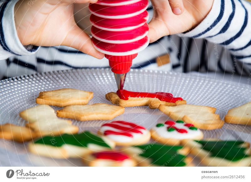Little kid decorating Christmas biscuits at Christmas day Dough Baked goods Dessert Candy Joy Happy Decoration Table Kitchen Feasts & Celebrations