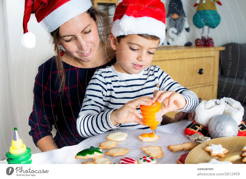 Mother and son decorating Christmas biscuits at home Woman Child Human being Christmas & Advent Beautiful White Red House (Residential Structure) Joy Winter
