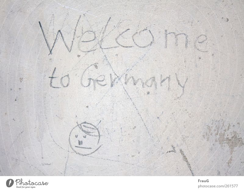 Welcome? Graffiti Small Town Wall (barrier) Wall (building) Facade Sign Characters Communicate Gray Disbelief Mistrust insecurity Colour photo Exterior shot