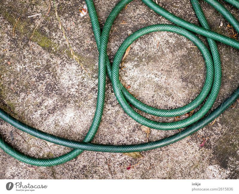 Green garden hose Living or residing Garden Deserted Terrace Garden hose Lie Whorl Untidy Colour photo Exterior shot Day Light Contrast Bird's-eye view