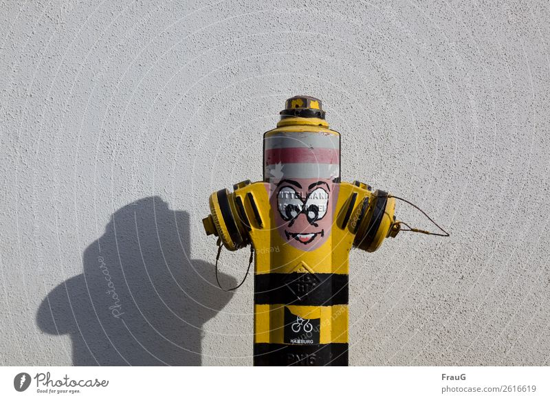 I used to be a hydrant. Face Subculture Facade Hat Fire hydrant Graffiti Stand Happiness Joy Art Shadow Colour photo Exterior shot Day