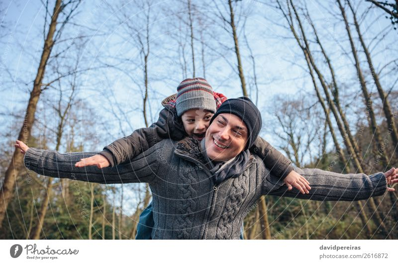 Man giving piggyback ride to happy kid in the forest Lifestyle Joy Happy Leisure and hobbies Playing Winter Child Boy (child) Adults Parents Father