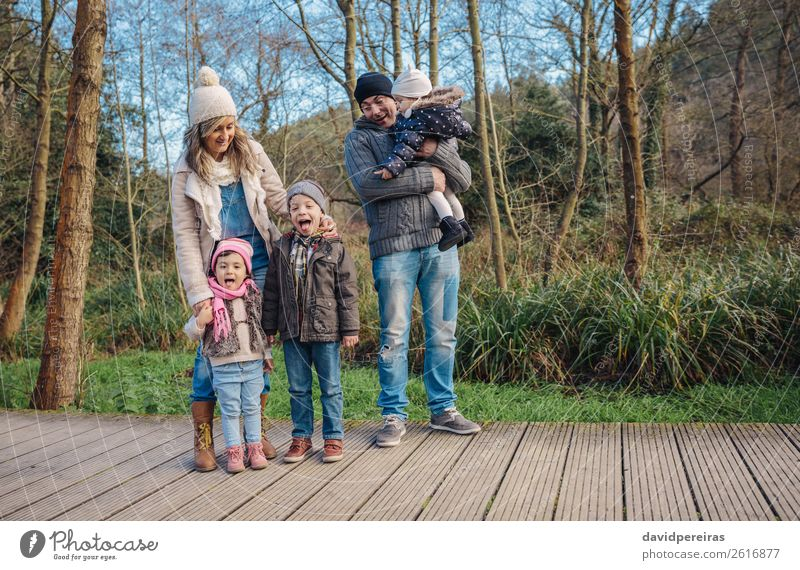 Happy family enjoying together leisure in the forest Woman Child Nature Man Green Tree Joy Forest Winter Lifestyle Adults Environment Love Boy (child)
