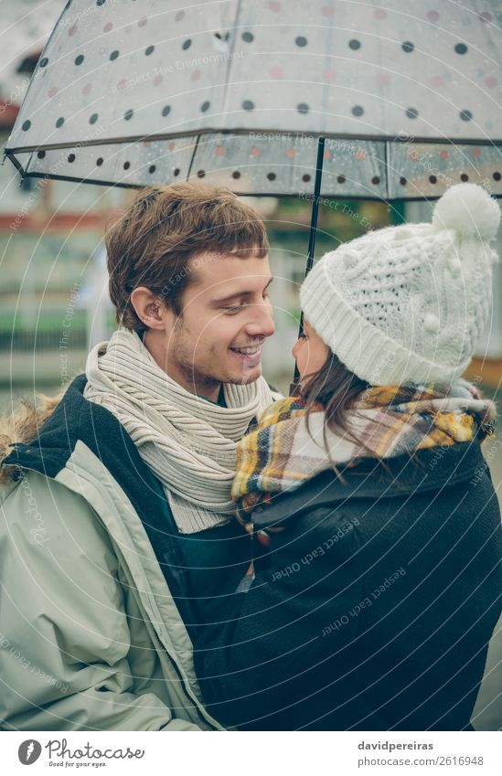 Young couple embracing outdoors under umbrella in a rainy day Lifestyle Happy Beautiful Winter Human being Woman Adults Man Family & Relations Couple Autumn