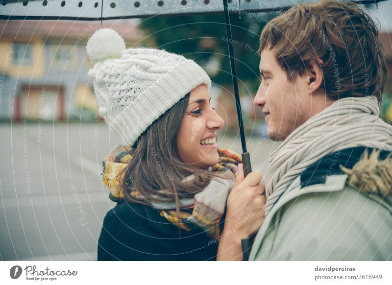 Young couple embracing and laughing outdoors under umbrella Lifestyle Happy Beautiful Winter Human being Woman Adults Man Family & Relations Couple Autumn Rain