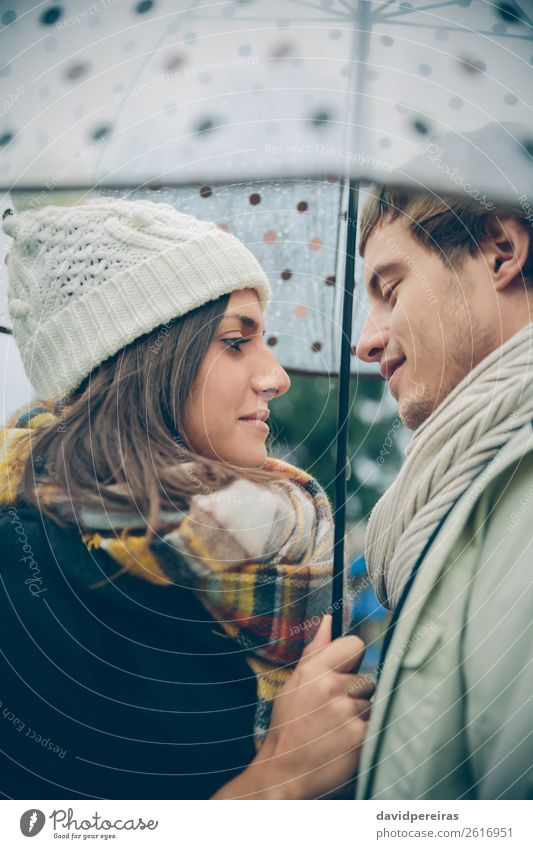 Young couple looking at each other under umbrella outdoors Lifestyle Happy Winter Human being Woman Adults Man Family & Relations Couple Autumn Rain Street