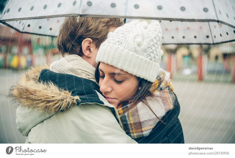 Young couple embracing outdoors under umbrella in a rainy day Lifestyle Beautiful Winter Human being Woman Adults Man Family & Relations Couple Autumn Rain