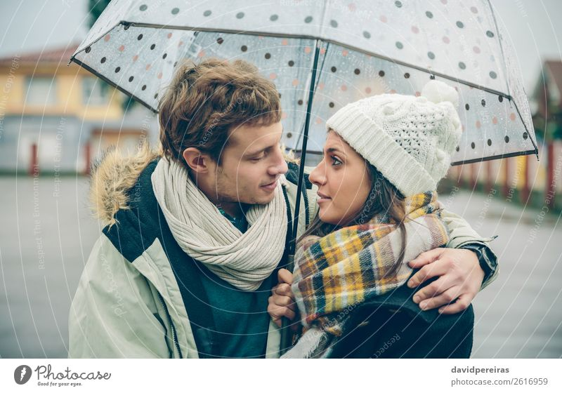 Young couple embracing under umbrella in an autumn rainy day Lifestyle Happy Beautiful Winter Human being Woman Adults Man Family & Relations Couple Autumn Rain