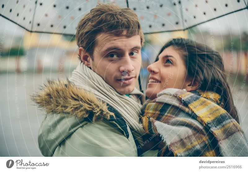 Happy couple embracing outdoors under umbrella in rainy day Lifestyle Beautiful Winter Human being Woman Adults Man Family & Relations Couple Autumn Rain Street