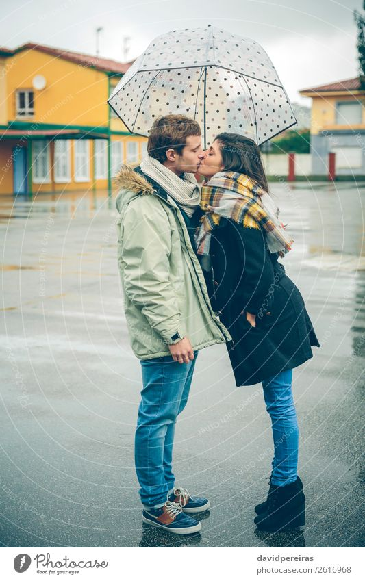 Young couple kissing outdoors under umbrella in a rainy day Lifestyle Beautiful Winter Human being Woman Adults Man Family & Relations Couple Autumn Rain Street