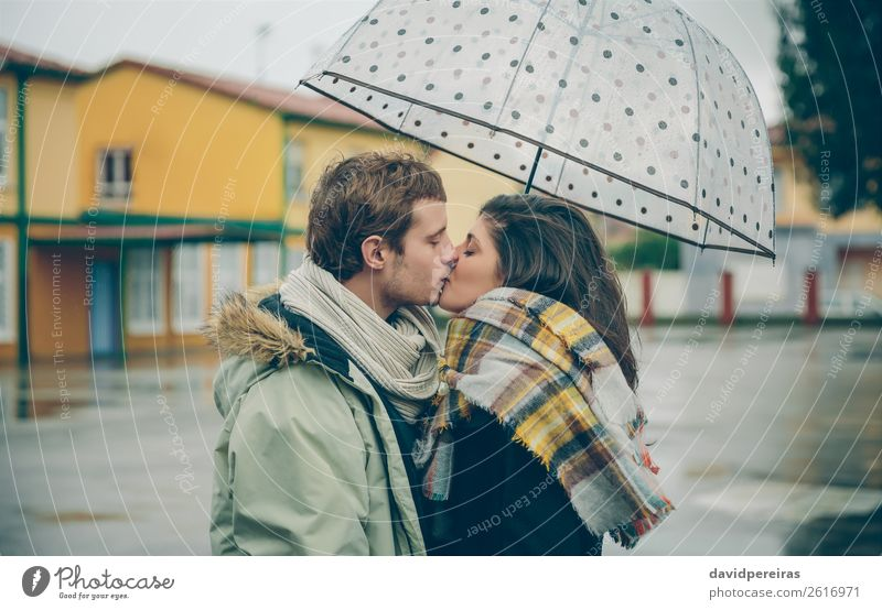 Young couple kissing outdoors under umbrella in a rainy day Lifestyle Happy Beautiful Winter Human being Woman Adults Man Family & Relations Couple Autumn Rain