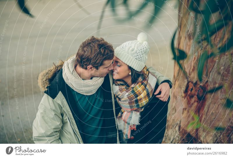 Young couple in love embracing and kissing outdoors Lifestyle Happy Beautiful Winter Human being Woman Adults Man Family & Relations Couple Autumn Rain Tree