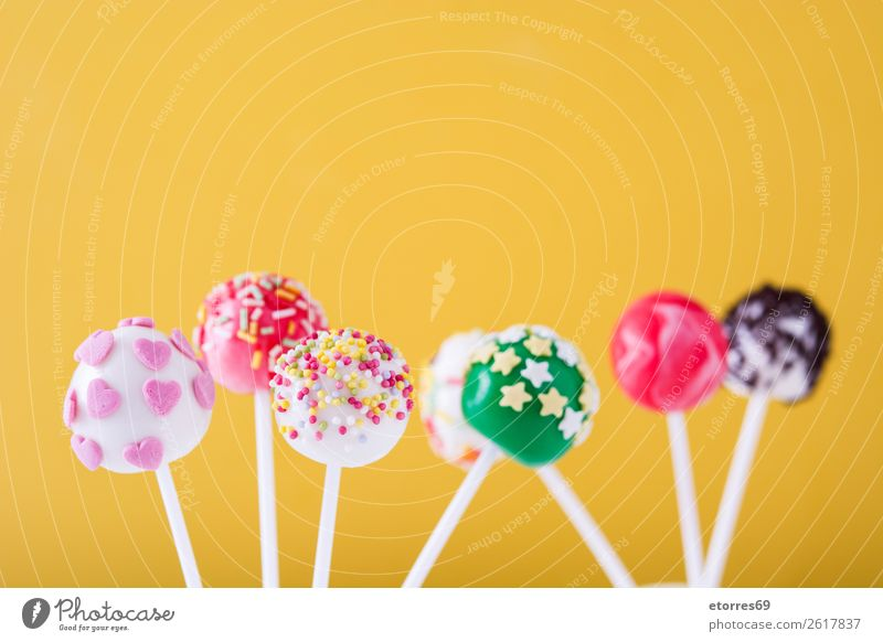 Sweet cake pops on yellow background Baked goods Cake Candy Colour Multicoloured Food Food photograph Lollipop Baking Yellow Dog food stick Pink Dessert Bright