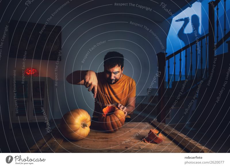 man cutting halloween pumpkin Lifestyle Joy Happy Face Leisure and hobbies Decoration Kitchen Feasts & Celebrations Hallowe'en Man Adults Family & Relations