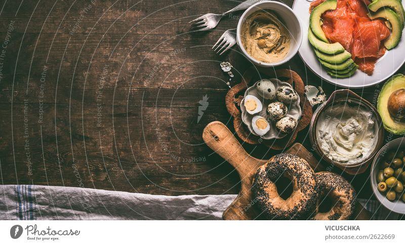 Home breakfast preparation with bagel bread, salmon, avocado , fresh cheese, hummus and cooked quail eggs on dark rustic wooden background, top view. Copy space for your design, banner
