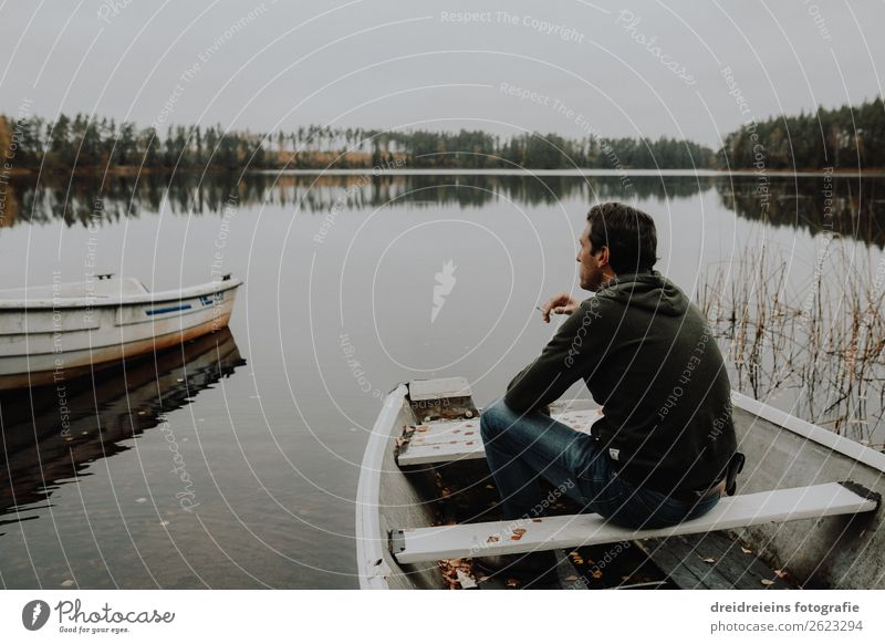 Man sits at sea in a rowboat smoking a cigarette. Adventure Freedom Masculine Adults 1 Human being Landscape Spring Summer Autumn Coast Lakeside Relaxation