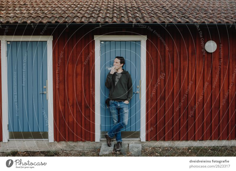 Man stands in front of Schwedenhaus log cabin and smokes cigarette Lifestyle Human being Masculine Adults Hut Smoking Stand Hip & trendy Self-confident