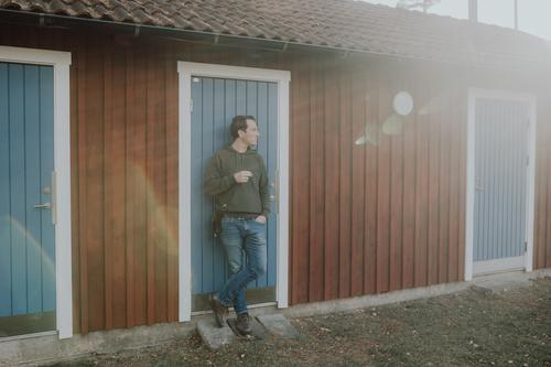 Man smokes cigarette in the sunlight in front of a house in Sweden Lifestyle Smoking Masculine Environment Sunlight Spring Summer Autumn Beautiful weather Hut