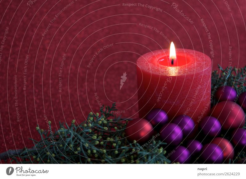 Red candle with christmas decoration I Feasts & Celebrations Christmas & Advent Religion and faith Moody Candle 1 Flame Copy Space Glitter Ball Violet Green
