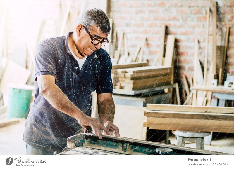 Carpenter cutting wooden board at his workshop Human being Man Hand Adults Wood Building Business Work and employment Metal Industry Safety Concentrate Desk