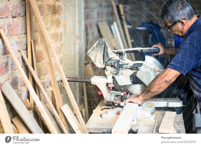 Professional carpenter with circular saw Human being Man Hand House (Residential Structure) Adults Wood Building Work and employment Metal Technology Industry